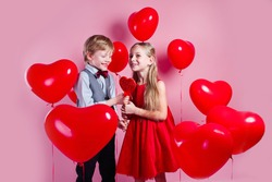 Funny boy and little girl with candy red lollipop in heart shape. Beautiful children eat sweets on red heart background. Valentine's day concept