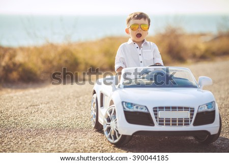 Funny boy car driver with the steering wheel. year-old boy in a white shirt in a red toy car in the street. Little boy driving big toy car and having fun, outdoors. Young kid portrait with toy car