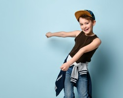 Funny boy in stylish cap jumping in place looking down under feet with roguish smile. Childhood, sly kid, troublemaker. Three quarter length portrait isolated on blue background. Copy space