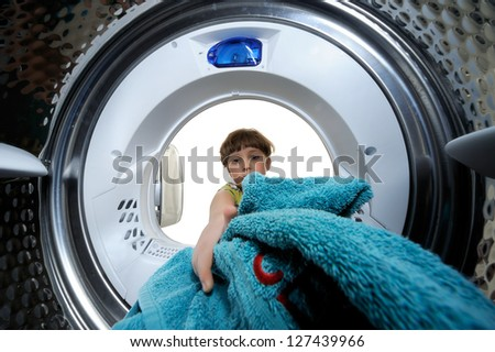 Funny boy loading clothes to washing machine. View from the inside of washing machine.