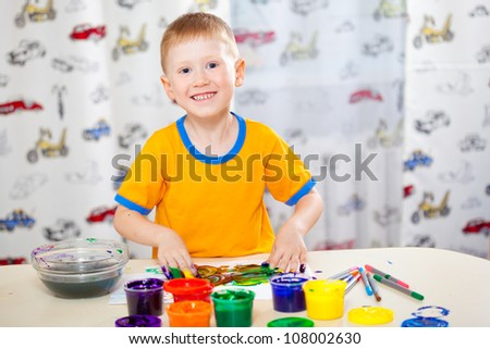 funny boy with painted fingers, painting at home