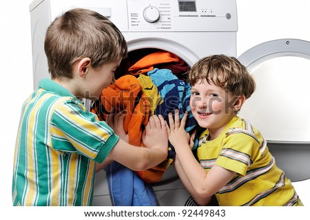 Funny boys loading clothes to washing machine.