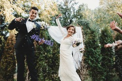 Funny bride and groom jump up holding a lettering with wedding hashtag in their arms