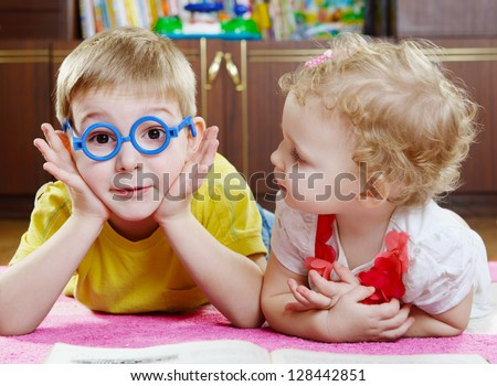 Funny brother in toy glasses with baby sister on floor