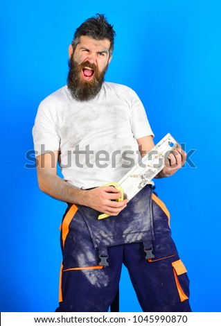 Funny buider concept. Guy with beard covered with dust. Builder, worker, carpenter, handyman with shouting face holds saw or hacksaw, blue background. Man play with saw like guitar, rest and relax.