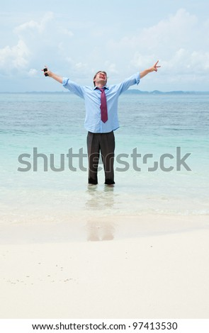 Funny business man calling by cell phone on the beach - stock photo