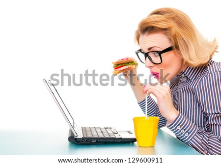 Funny business woman holding sandwich and drinking juice, isolatd on white. Studio shot