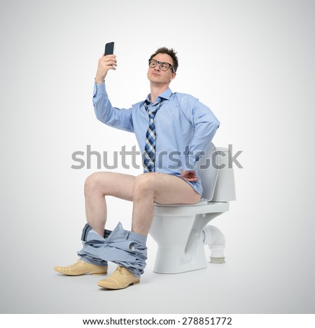 Funny businessman photographing himself in the toilet. Selfie everywhere concept