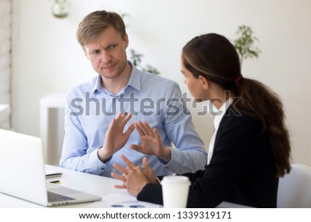 Funny businessman rejecting to give interview to journalist. Stop sign. Man from recruitment management stopping interviewing lady, fraud, unhappy customer complaining, demanding compensation