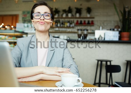 Funny businesswoman with pencil between her upper lip and nose sitting in cafe