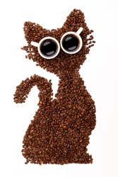Funny cat made of roasted coffee beans and two cups on white background. Creative concept photo of cat made of roasted coffee beans. Black cat from beans. Top view.