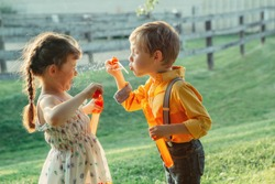 Funny Caucasian children girl and boy blowing soap bubbles in park at summer sunset. Real authentic happy childhood moment of friendship. Lifestyle activity for friends siblings.