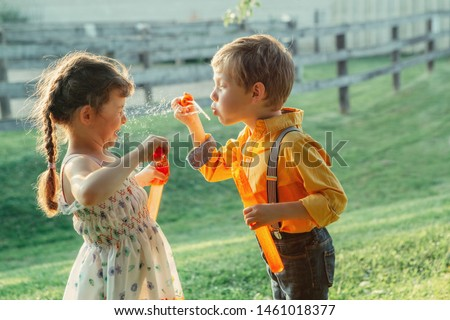 Funny Caucasian children girl and boy blowing soap bubbles in park at summer sunset. Real authentic happy childhood moment of friendship. Lifestyle activity for friends siblings. #1461018377