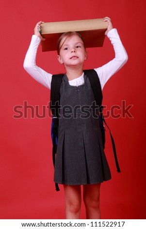 funny caucasian schoolgirl with backpack and heavy book over bright red background