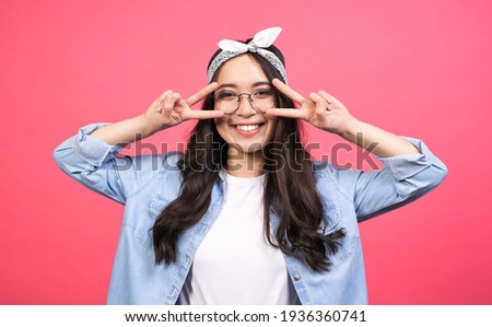 Funny cheerful asian teenage girl, with long black hair, in a denim shirt and round glasses, shows a sign of peace near the eyes, calls for peace, against war, posing on a pink background.