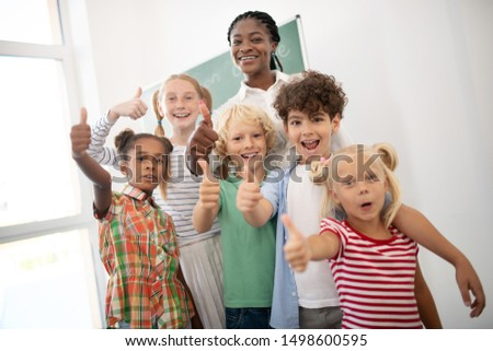 Funny cheerful children. Funny cheerful children showing thumbs up while feeling amazing after lesson #1498600595