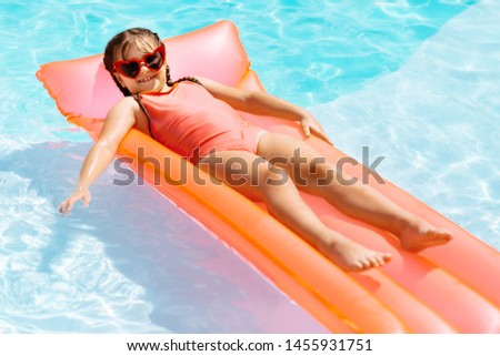 Funny cheerful girl. Funny cheerful girl wearing bright sunglasses smiling while chilling in swimming pool #1455931751
