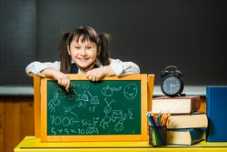 Funny cheerful little schoolgirl draws with chalk on a matte chalk board. Mathematics, arithmetic, numbers in elementary school.