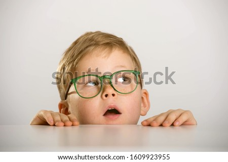 Funny child boy looking while hiding behind table. Kid in glasses.  Stock photo ©