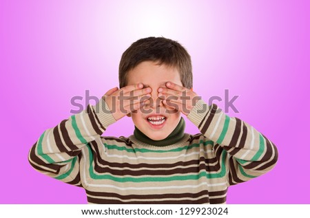 Funny child covering his eyes on a pink background