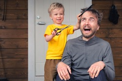 Funny child cutting hair to his father at home during quarantine lockdown. Little hairdresser barber makes haircut to his scared bearded dad. Beauty and selfcare at home lifestyle concept.