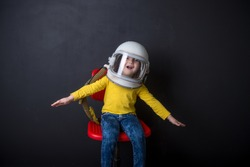 Funny child dressed in an astronaut helmet costume. Little girl in space suit. Success, bright idea, creative ideas and innovation technology concept. Kindergarten and preschool education. Autism