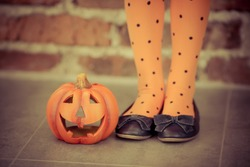 Funny child dressed witch costume holding pumpkin. Halloween holidays concept