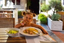 Funny child girl eats healthy food outside at restaurant. Kids menu