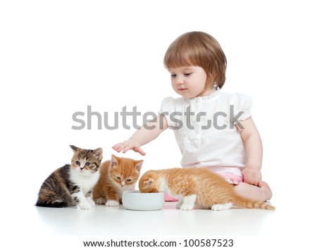 funny child girl feeding attractive kitten