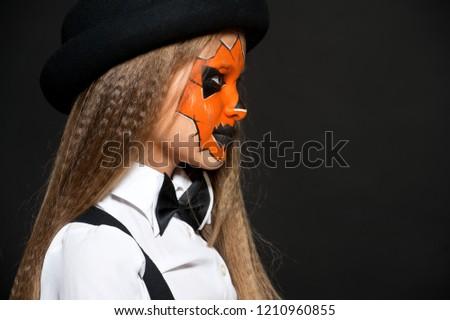 Funny child girl in pumpkin costume for Halloween. Halloween makeup. Face art. #1210960855