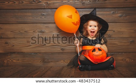 funny child girl in witch costume for Halloween with pumpkin Jack and orange balloon on a dark wooden background