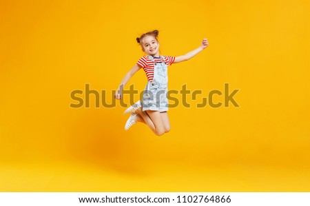 Photo of funny child girl jumping on a colored yellow background