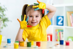 Funny child girl with hands painted in colorful paint at home
