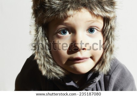 Funny child in fur Hat.casual winter style.close-up portrait of little boy.children emotion.hat ear flaps.Big blue eyes #235187080