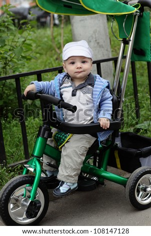 Funny child is on tricycle in a summer park