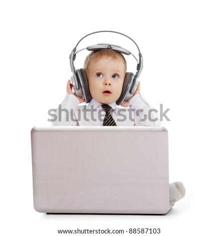 Funny child playing with laptop and listening to music in headphones