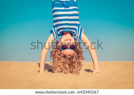 Funny child standing upside down on sandy beach. Happy kid playing outdoor. Girl having fun on summer vacation. Active healthy lifestyle concept