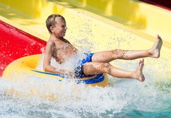 Funny child taking a fast water ride on a float splashing water. Summer vacation concept.