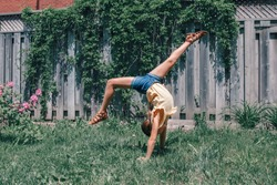 Funny child teenage girl doing cartwheel on backyard. Excited joyful kid playing outdoor. Happy lifestyle childhood and freedom spirit concept. Seasonal sport activity for children.
