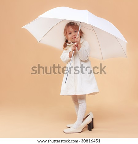Funny child wearing adult shoes posing with umbrella