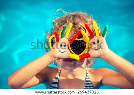 Funny child with drawing smiley on hands in swimming pool Summer vacation concept