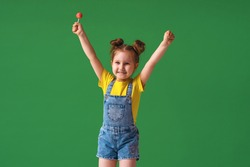 funny child with raised hands in the air. a 4-year-old girl with a Lollipop is funny, emotionally happy. naughty little girl on a green background in the Studio posing with pleasure.