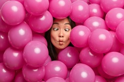 Funny childish young Asian woman makes fish lips crosses eyes foolishes around while decorating hall with inflated balloons for special occasion has crazy weird face. People and holidays concept