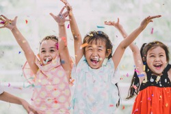 Funny Children girls celebrate smile and have fun, Happy kids colorful confetti in party.