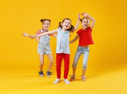 funny children girls jumping on a colored yellow background