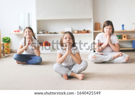 Funny children of different ages in a bright children's center do yoga, asana in the lotus position. Lifestyle yoga in a bright playroom Stok fotoğraf ©