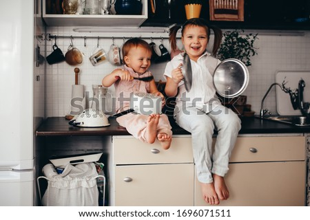 Funny children play music on kitchen tools, loud children make noise in the kitchen, children are quarantined at home ストックフォト ©