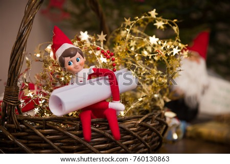 Funny Christmas dwarf toy with rolled paper sitting on the basket near Christmas tree, Preparations for holiday season and celebration.   #760130863