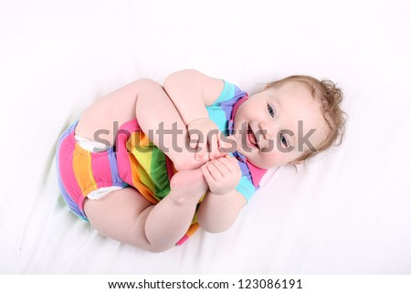 Funny chubby baby girl playing with her feet