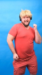Funny chubby freak man in headphones and a wig in a pink t-shirt dances and laughs on a blue background, vertical. High quality photo
